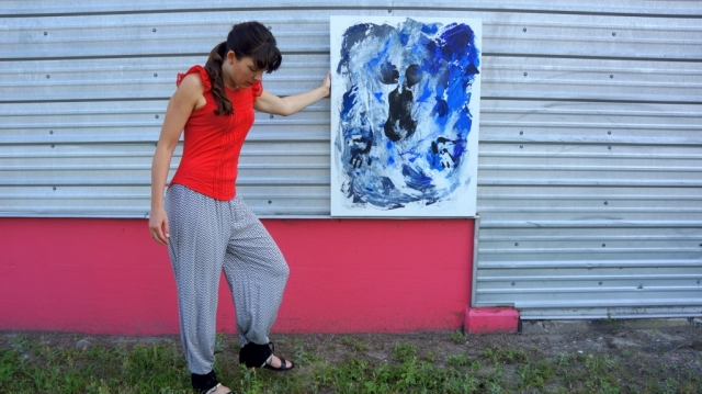 "Artist Rachael Harbert next to a pink and metal wall holding abstract expressionism painting ""Under Water"""