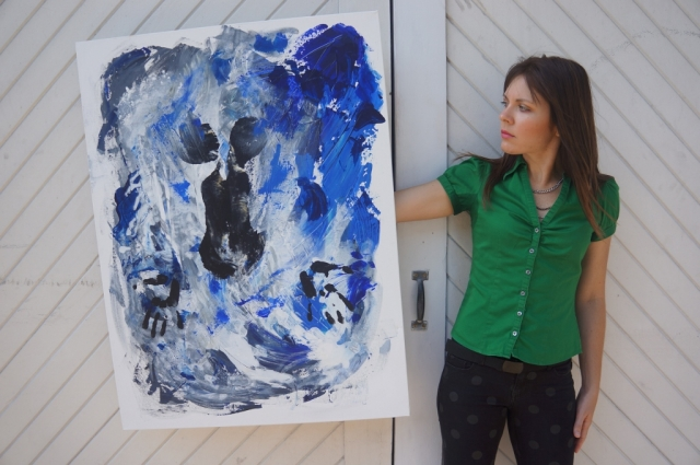 "Artist Rachael Harbert next to white double doors holding abstract expressionism painting ""Under Water"""