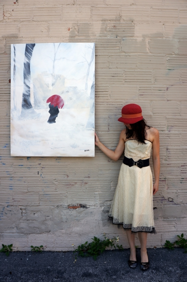 "Artist Rachael Harbert wearing a red hat standing in front of a block wall with painting ""White Storm"" as she looks down at the ground"