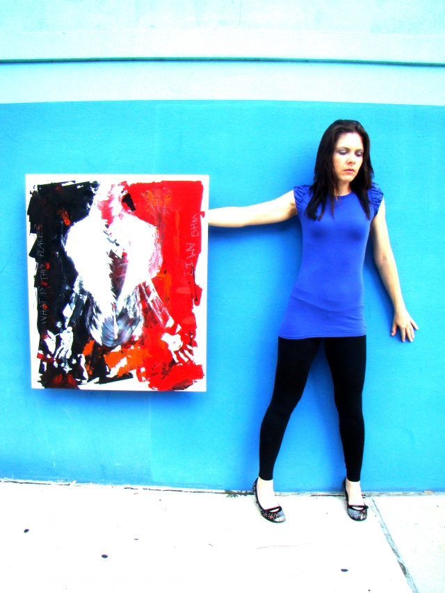 """Artist Rachael Harbert holds painting """"Who Am I"""" in front of a bright two-toned blue wall"""