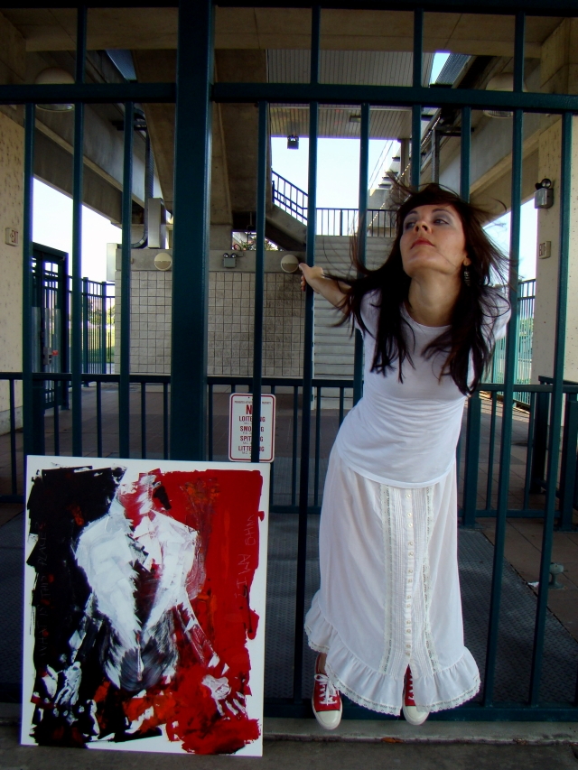 """Artist Rachael Harbert hanging off bars at a skyway station as painting """"Who Am I"""" leans against the bars"""