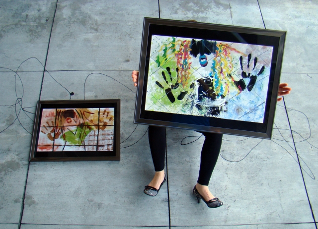 "Artist Rachael Harbert holds abstract expressionism painting ""Retro Girl"" as she sits on a concrete sidewalk"