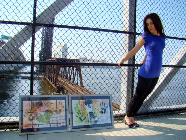 "Artist Rachael Harbert stands next to abstract expressionism painting ""Retro Girl""  on a railroad overpass"