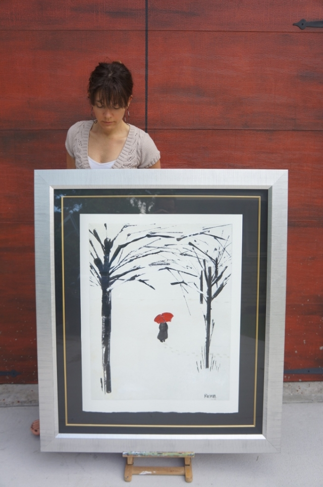 """Artist Rachael Harbert in front of a garage door propping up large framed print of """"A Lonely Walk"""""""