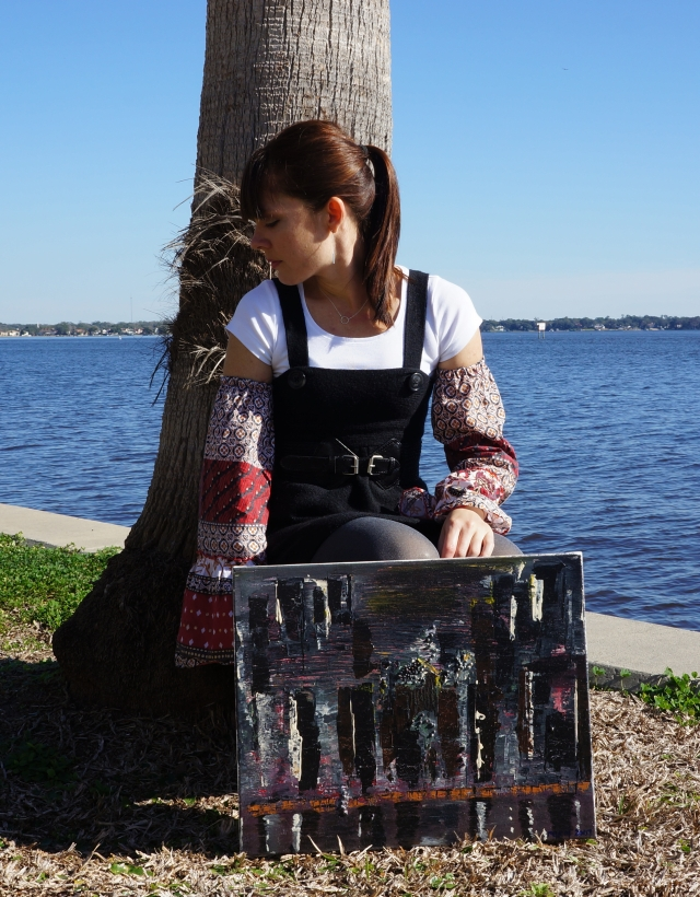 "Artist Rachael Harbert squatting along the bank of a river with abstract painting ""Alive at Night"""