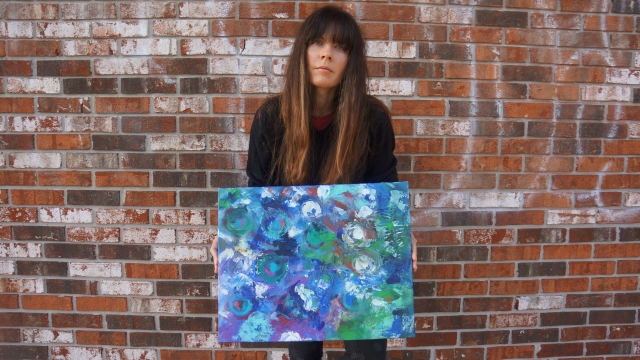 Artist Rachael Harbert holding painting Alliums in front of a brick wall