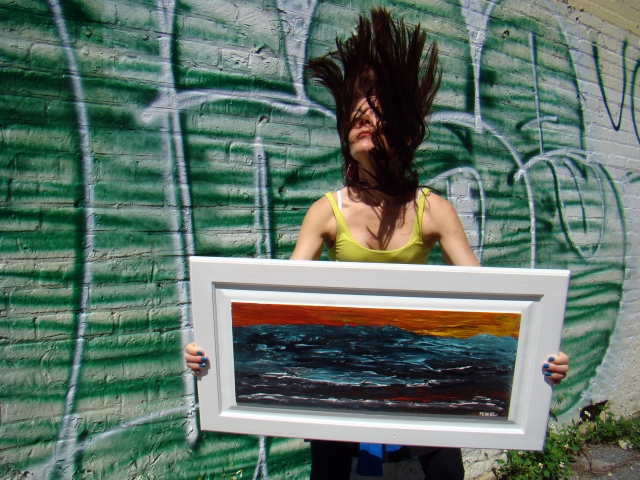 "Artist Rachael Harbert flipping her hair next to a green graffiti wall with abstract painting ""Angry Sea"""