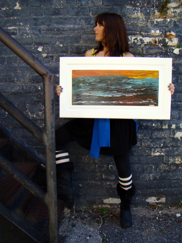 "Artist Rachael Harbert next to iron staircase holding abstract painting ""Angry Sea"""
