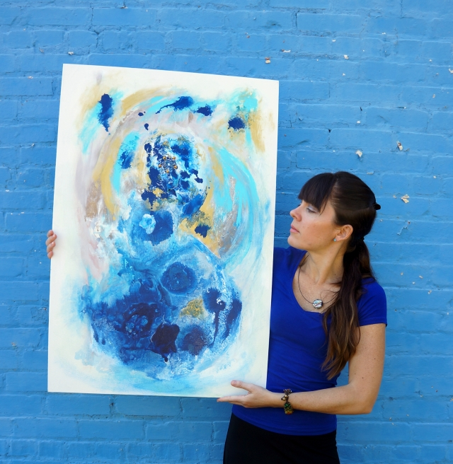 Artist Rachael Harbert holds painting Aqua Gold in front of a blue brick wall