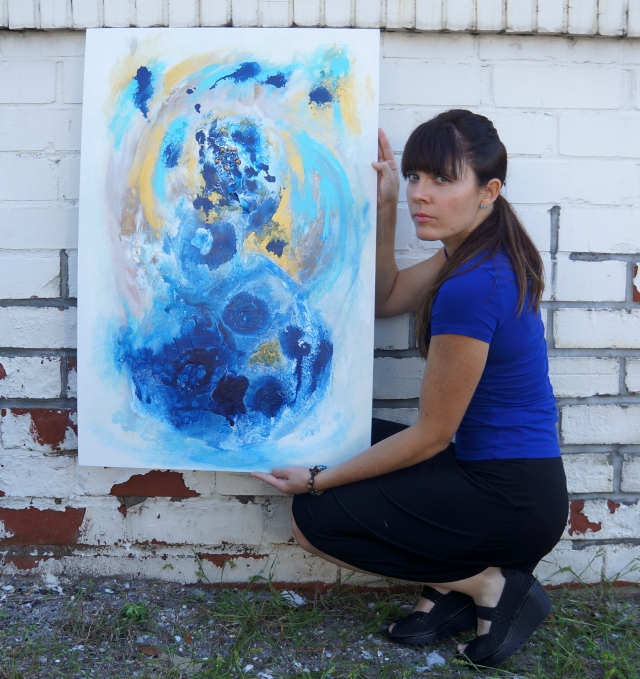 Artist Rachael Harbert holds painting Aqua Gold in front of a rustic white brick wall