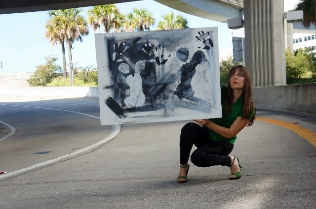 """Artist Rachael Harbert holds abstract painting """"Black and White"""" as she crouches on a highway on ramp"""