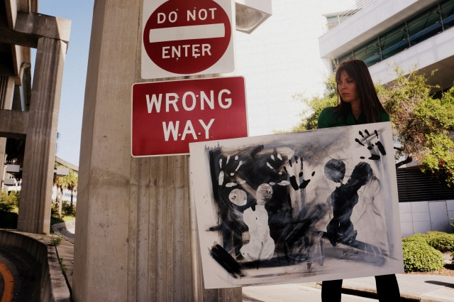 "Artist Rachael Harbert holds abstract painting ""Black and White"" as stands on a wall of a highway overpass"
