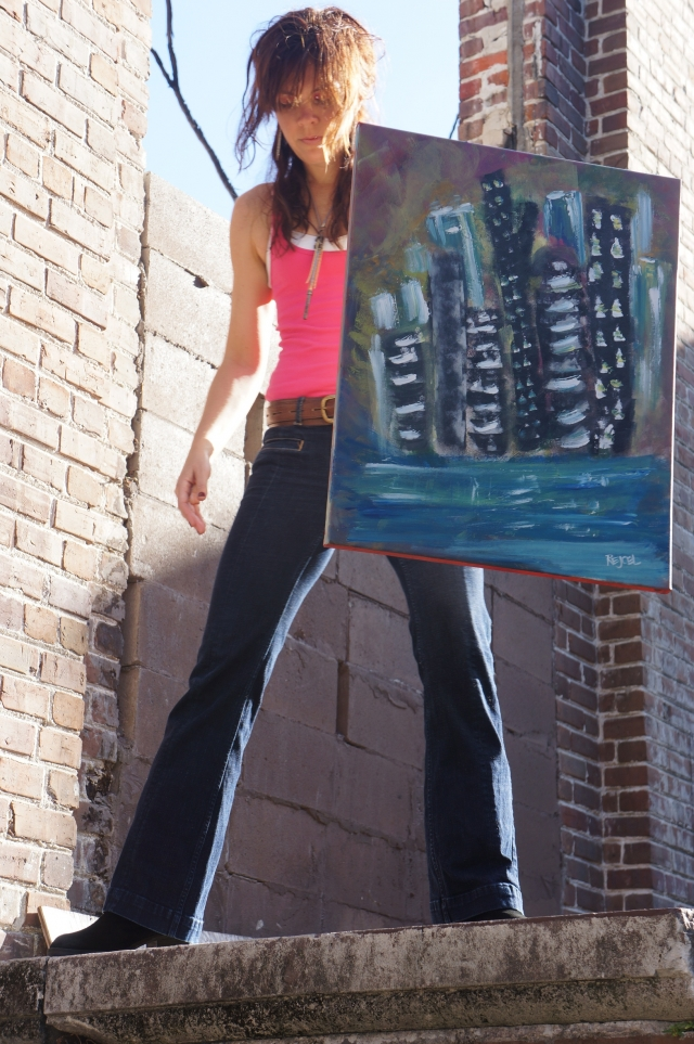 "Artist Rachael Harbert stands on a wall surrounded by brick ruins holding painting ""Blue City"""