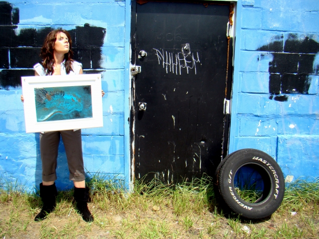 "Artist Rachael Harbert holding abstract painting ""Alogo"" while standing next to a blue wall and black door"