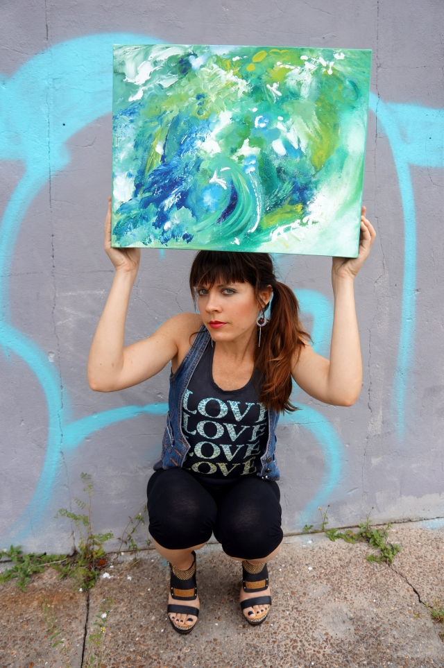 "Artist Rachael Harbert holding abstract painting ""Blue and Green Cosmos"" in front of a wall with aqua graffiti"