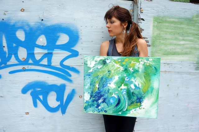 "Artist Rachael Harbert holding abstract painting ""Blue and Green Cosmos"" in front of a wall with blue and green graffiti"