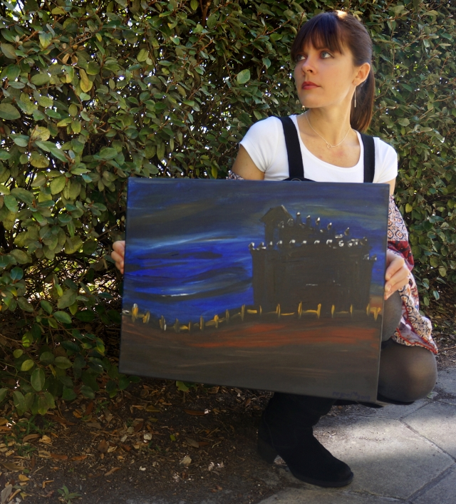 "Artist Rachael Harbert holds abstract painting ""Blue Night"" in front of bushes"