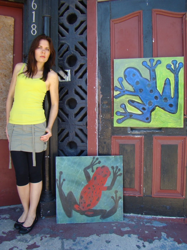 "Artist Rachael Harbert leaning on a red and black door with pop art painting ""Blue Poison"" hanging on the door"