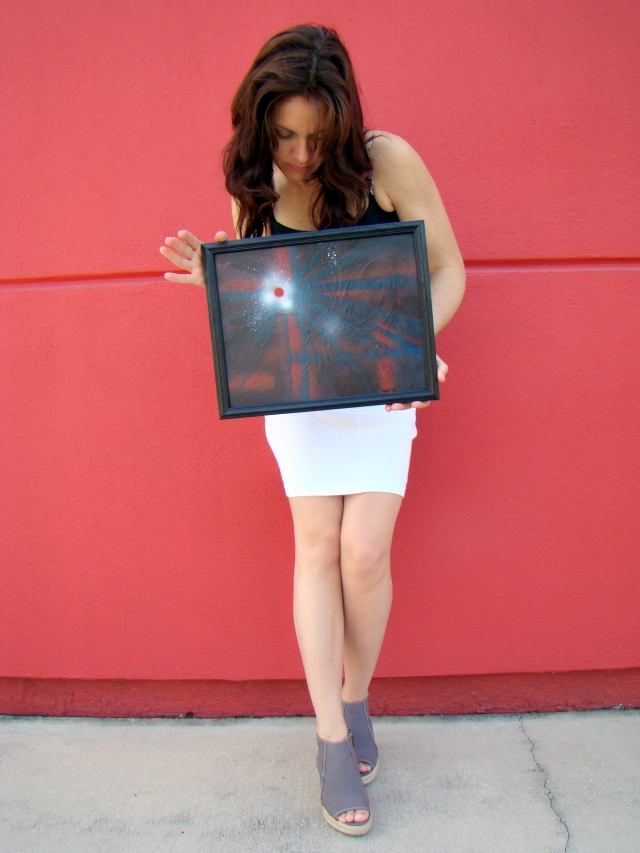 "Artist Rachael Harbert holds abstract painting ""Bullet Hole"" in front of a red wall"