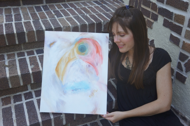 "Artist Rachael Harbert holds abstract painting ""Caribbean Flamingo"" as she leans on brick steps"
