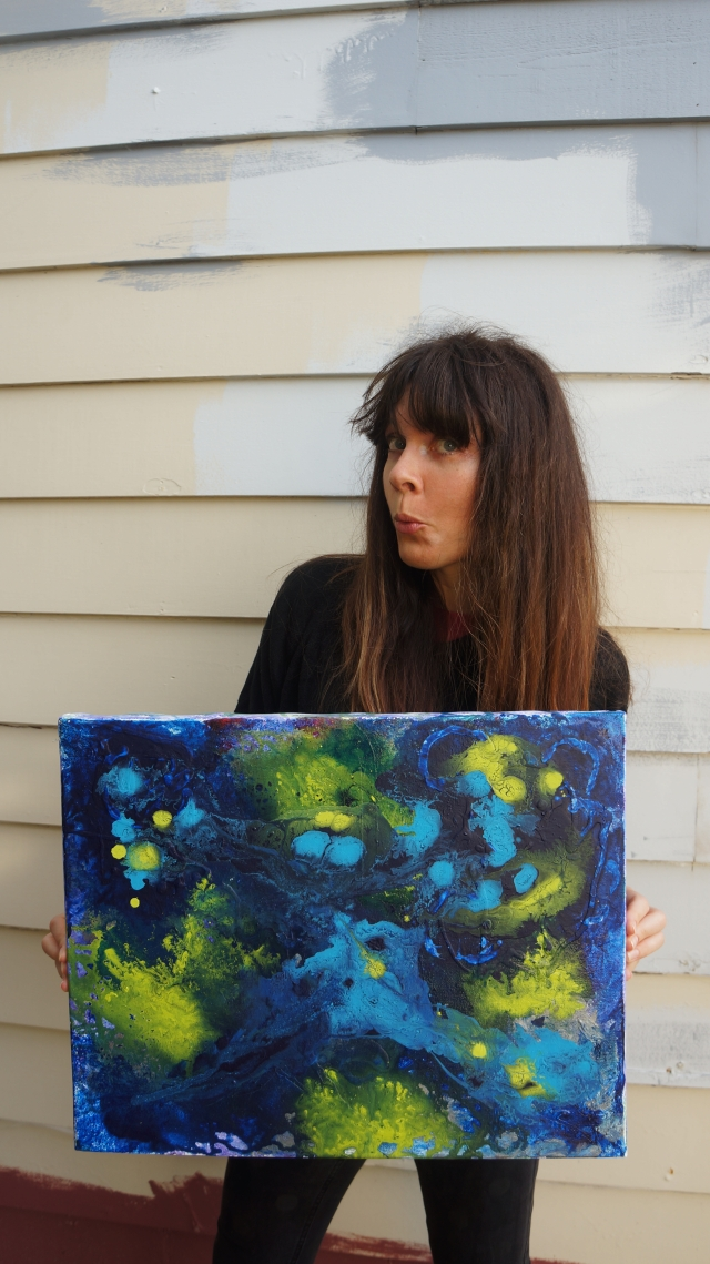 Artist Rachael Harbert holds painting Cerulean Blue in front of a wall with patches of different colors