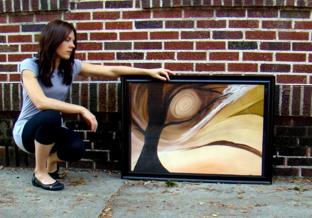 "Artist Rachael Harbert leans down next to a brick wall as she props up abstract painting ""Chocolate"""