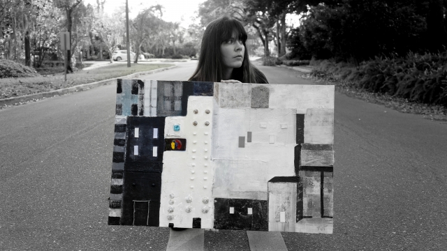 Artist Rachael Harbert holds painting City Blocks as she crouches in the middle of a street