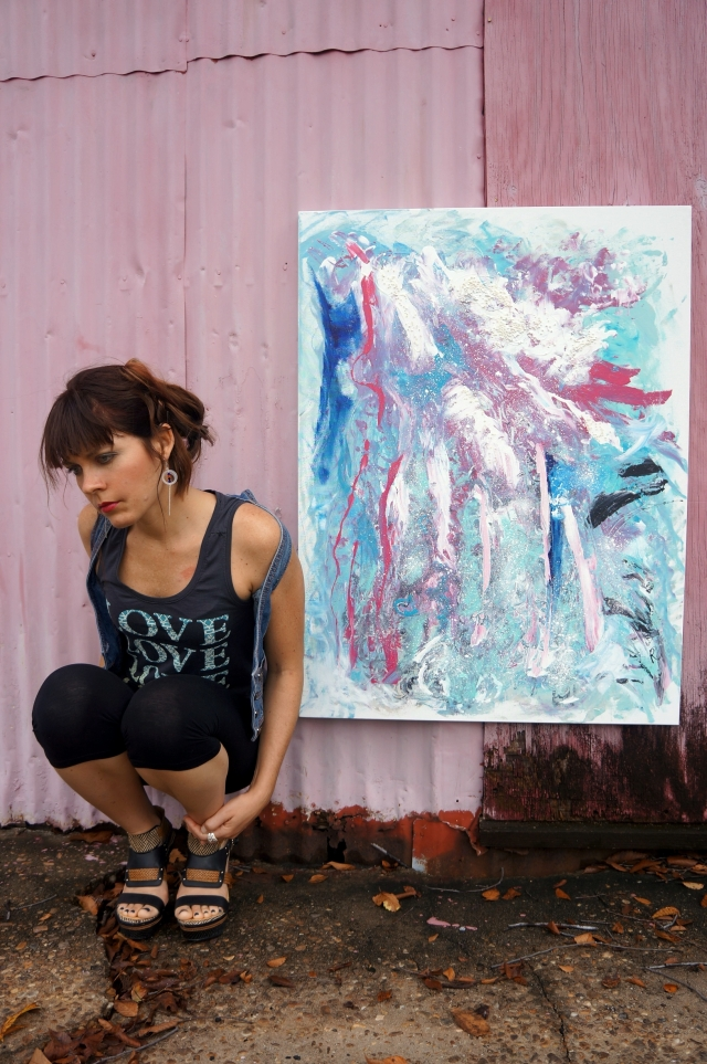 "Artist Rachael Harbert kneeling next to a pink metal wall with abstract painting ""Cool Blast"" hanging on the wall"