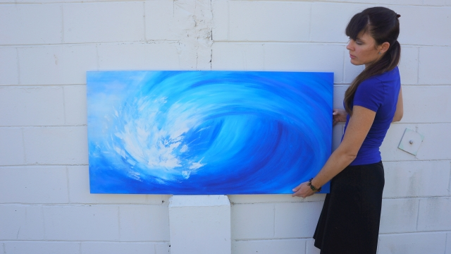 Artist Rachael Harbert holds painting Crashing Wave in front of a white cement block wall