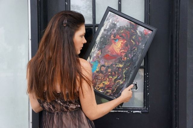 "Artist Rachael Harbert holding abstract painting ""Ebony"" in front of a black door"