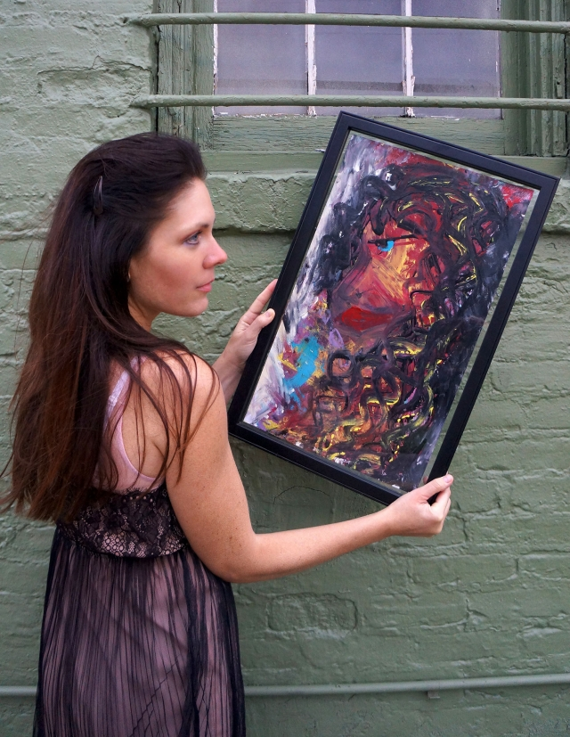 "Artist Rachael Harbert holding abstract painting ""Ebony"" in front of a green wall with iron window guards"