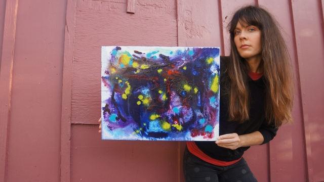 Artist Rachael Harbert holds painting Electric Pulses in front of a burgundy wall