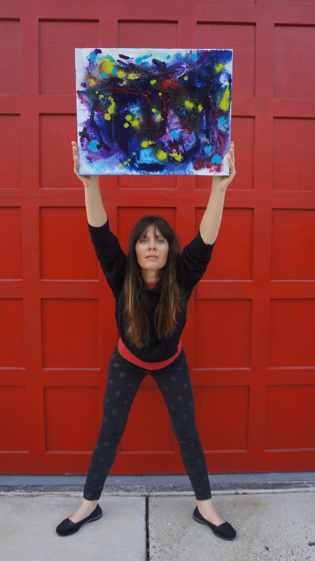 Artist Rachael Harbert holds painting Electric Pulses in front of a huge red firestation door
