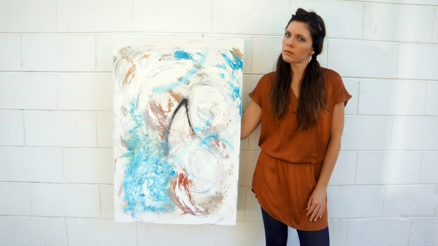 Artist Rachael Harbert holds painting Fin in front of a white brick wall