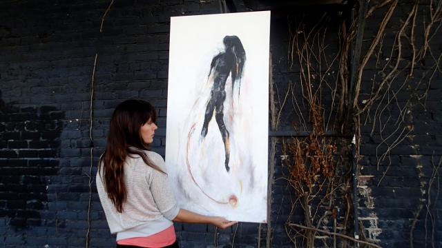 "Artist Rachael Harbert holds painting ""From Dust"" in front of a dark blue wall accessorized with dying vines"