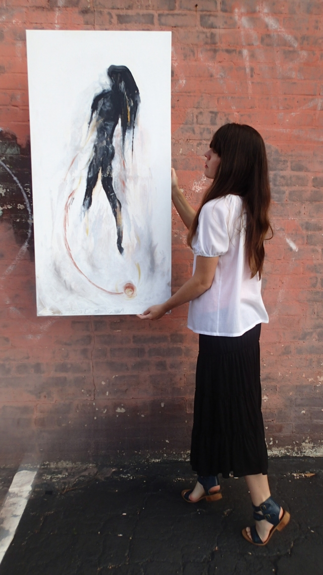 "Artist Rachael Harbert holds painting ""From Dust"" in front of a coral brick wall"