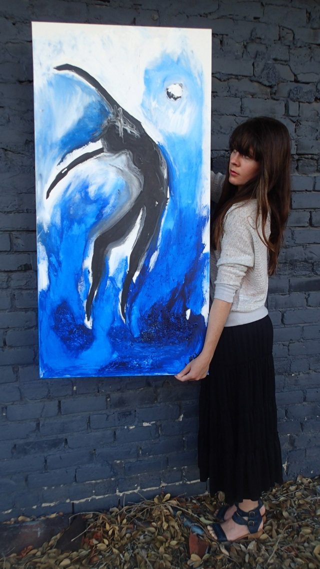 "Artist Rachael Harbert holds painting ""From Water"" in front of a dark blue wall"