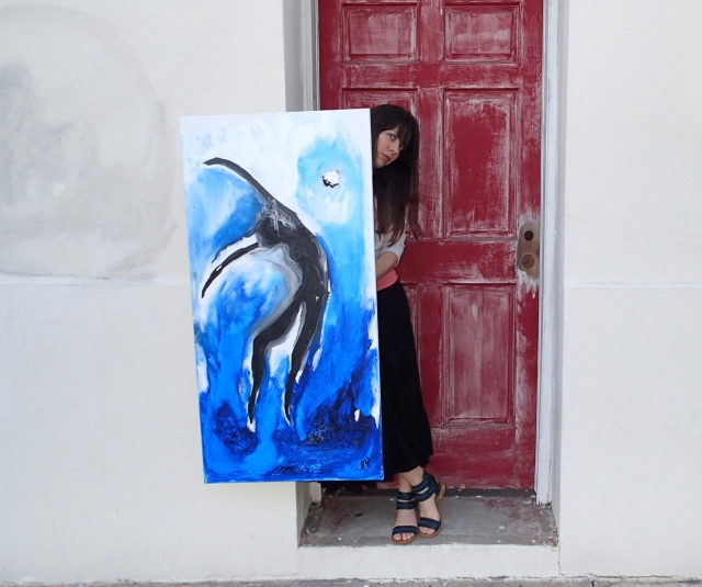 "Artist Rachael Harbert holds painting ""From Water"" in front of a red door"