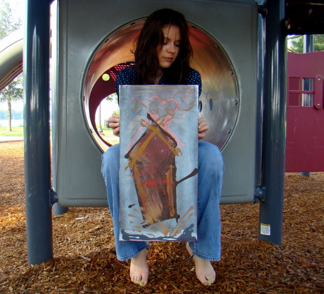"Artist Rachael Harbert sitting in playground tunnel holding abstract painting ""Gingerbread"""