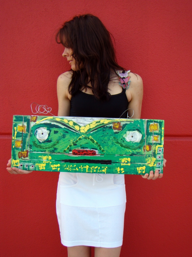 "Artist Rachael Harbert holding painting ""Grasshopper"" against a red wall"