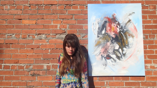Artist Rachael Harbert stands next to painting Inception as it hangs on a brick wall