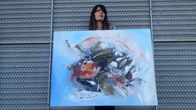 Artist Rachael Harbert holds painting Inception in front of a large chain door