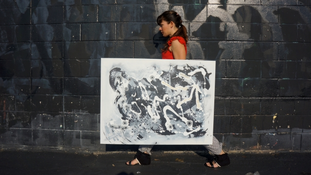 "Artist Rachael Harbert holds abstract painting ""Jumping Beans"" in front of a black wall with dark graffiti"