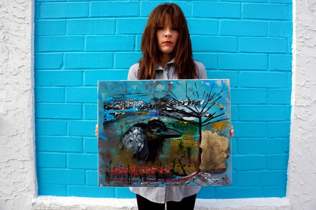 "Artist Rachael Harbert holds painting ""Little Black Crow"" in front of a blue wall"