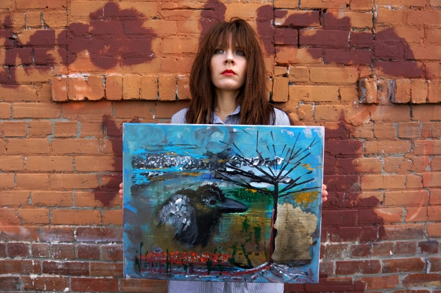 "Artist Rachael Harbert holds painting ""Little Black Crow"" in front of a brick building"