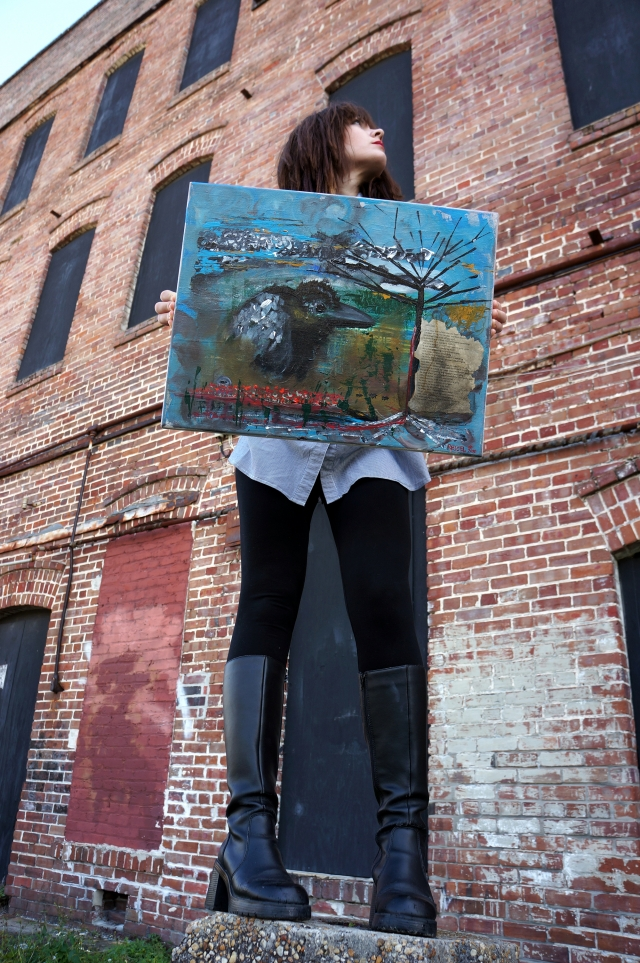 "Artist Rachael Harbert stands on a little brick wall and holds painting ""Little Black Crow"" in front of a brick building"