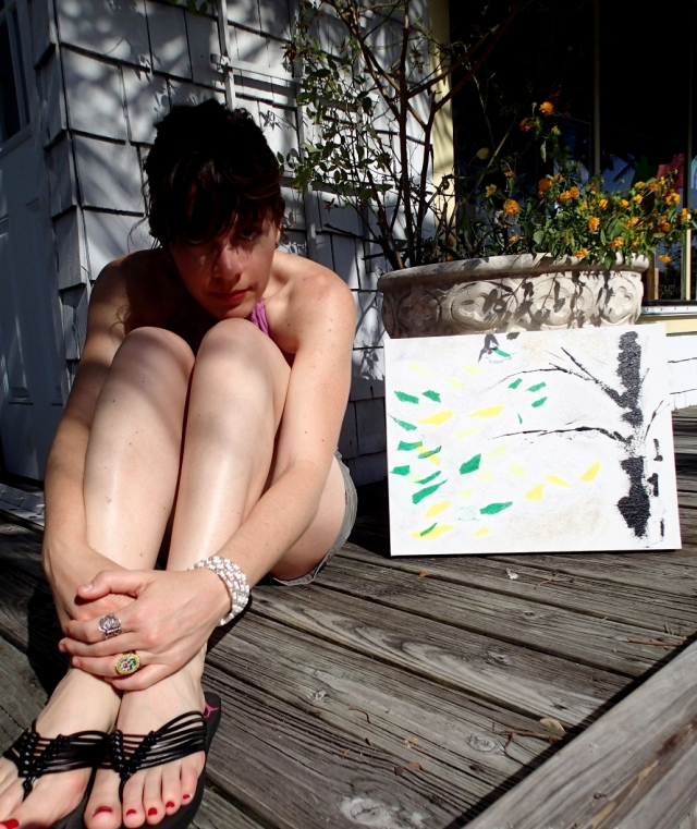 """Artist Rachael Harbert leans on her legs as painting """"Little Dancing Leaves"""" is propped next to her on a wooden deck"""