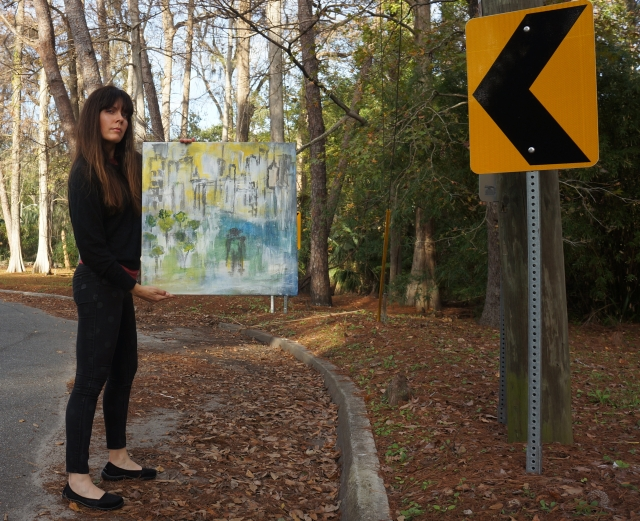 Artist Rachael Harbert holds painting The Man and the City as she stands in the middle of a street with road signs with large arrows