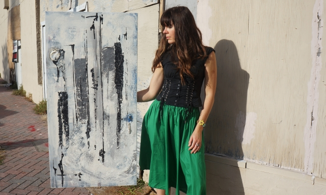 Artist Rachael Harbert holds painting Midnight Moon in the City as she stands on a sidewalk in front of dilapidated walls