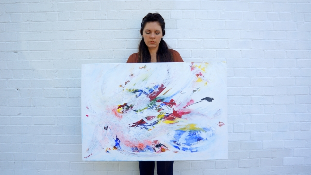Artist Rachael Harbert holds painting Pinata in landscape view while standing in front of a white block wall
